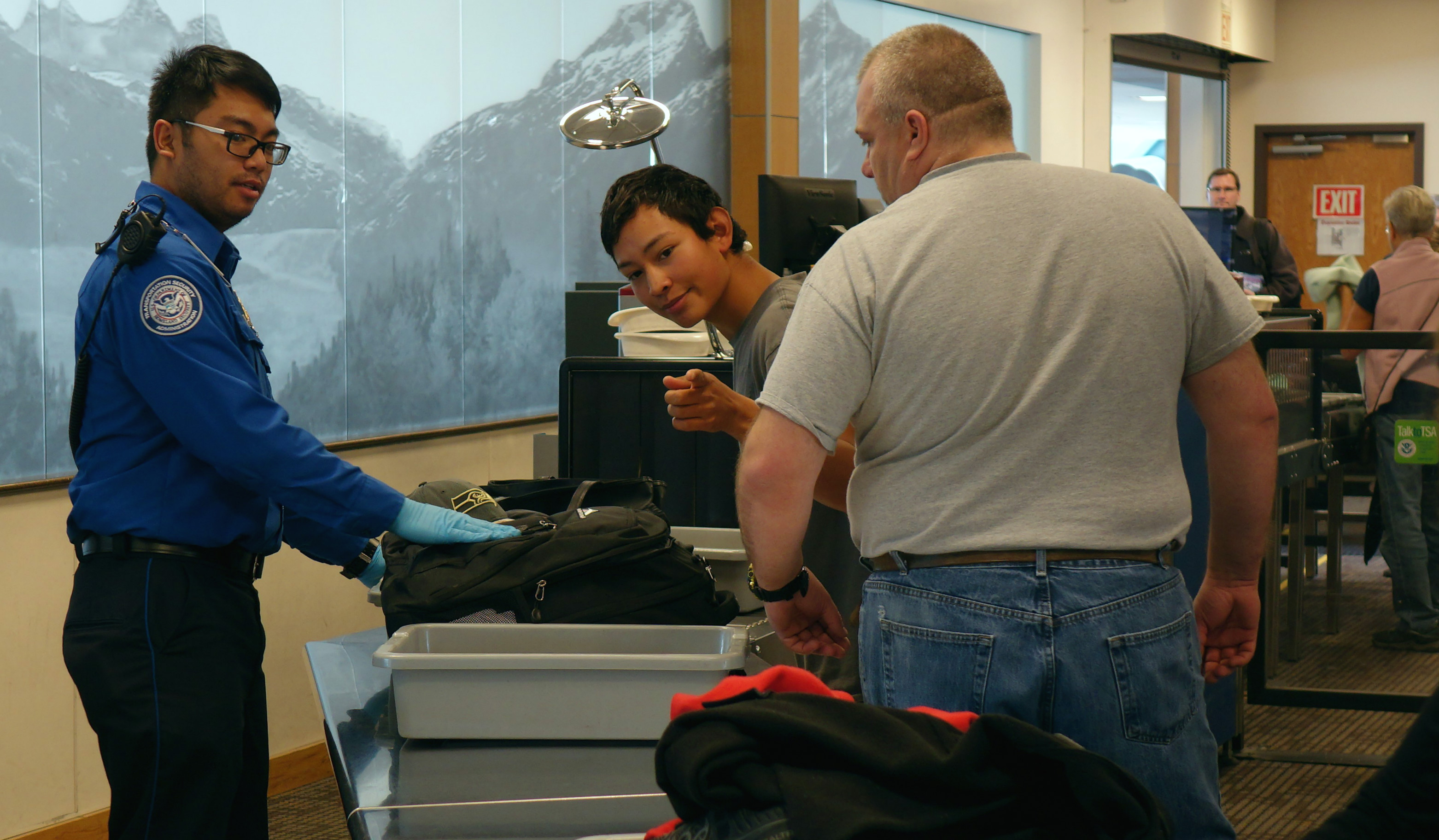 transportation security officer renier cava preps passengers carry on belongings for x ray