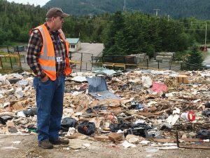 City of Ketchikan Solid Waste Superintendent Lenny Neely stands at the local landfill. He says discarded metal, construction material, bicycles and more are taken out of the dump through the city's salvage permit program. (Photo by Leila Kheiry, KRBD)