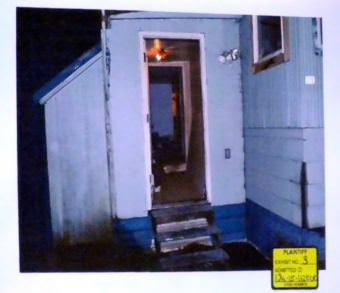 Photo of entry way of the mobile home at C-16 Kodzoff Acres Trailer Park is presented as evidence during the Christopher Strawn trial on Oct. 6, 2017. (Photo by Matt Miller/KTOO)