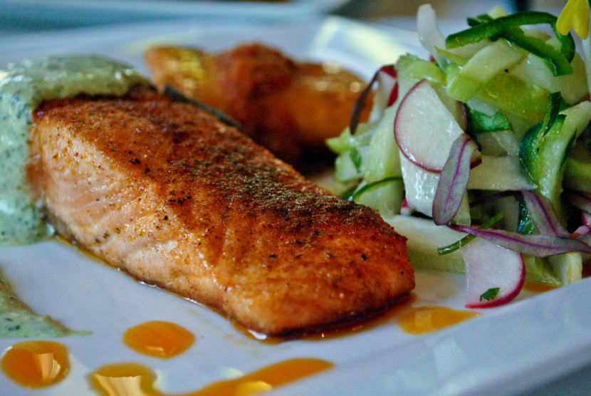 The Savory Street International Cafe in Sarasota, Florida, serves this ancho pepper crusted filet of salmon with a cilantro crema and a tomatillo, chayote, radish salad.