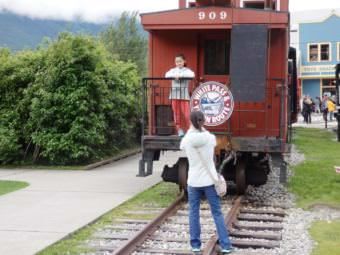 Tourists in Skagway take pictures with a White Pass and Yukon Route Railroad train car. (Photo by Emily Files/KHNS)