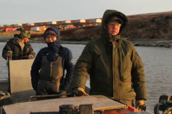 Residents of Newtok return from Mertarvik, seen in the background, the site the village hopes to move to. At right is tribal administrator Andrew John. (Photo by Rachel Waldholz/Alaska's Energy Desk)