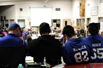 Thunder Mountain High School football players listen as other team members address the Board of Education over the plan to combine with Juneau-Douglas High School on Tuesday, Nov. 14, 2017. (Photo by Adelyn Baxter/KTOO)