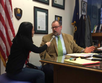 KTOO reporter Lisa Phu interviews District Attorney James Scott in January 2015 after he dropped the case against a Juneau woman for tripping traps. Scott's picture of Abraham Lincoln can be seen in the upper right.