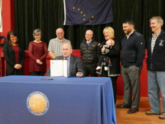 Alaska Gov. Bill Walker signs Senate Bill 28 on Thursday, November 16, 2017, at Petersburg's Sons of Norway Hall. Behind him are legislative staffer Melissa Kookesh, Petersburg community and economic development director Liz Cabrera, mayor Mark Jensen, Rep. Jonathan Kreiss-Tomkins, Petersburg harbormaster Glo Wollen and daughter Sigrid, legislative aide David Scott and lobbyist Ray Matiashowski. (Photo by Joe Viechnicki/KFSK)