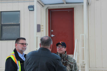 From left, Darryl Parks, chief of operations in civil engineering at JBER; Bob Sherrill of the Defense Logistics Agency; and Newtok Tribal Administrator Andrew John stand in front of one of the barracks units. (Photo by Rachel Waldholz/Alaska's Energy Desk)