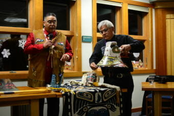 Roy Dennis, left, and Wayne Price tell the story of a boy eaten by sockeye salmon carved into a Tlingit hat. (Photo by Berett Wilber/KHNS)