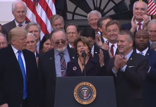 President Donald Trump congratulates U.S. Sen. Lisa Murkowski on passage of a bill to open the coastal plain of the Arctic National Wildlife Refuge to oil drilling. Rep. Don Young and Sen. Dan Sullivan flank Murkowski at the mic. (Video screenshot courtesy White House)