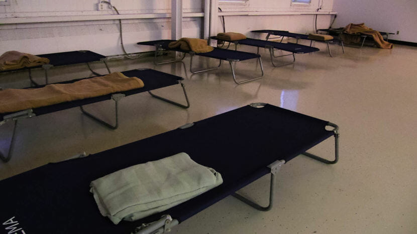 A Row Of Dark Colored Cots Along The Walls Of A Room With A Single Blanket
