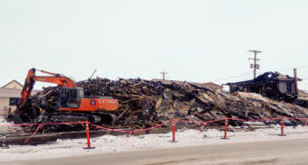 What remains of the Polaris Hotel in Nome is being demolished and removed by Q Trucking. (Photo by Davis Hovey/KNOM)