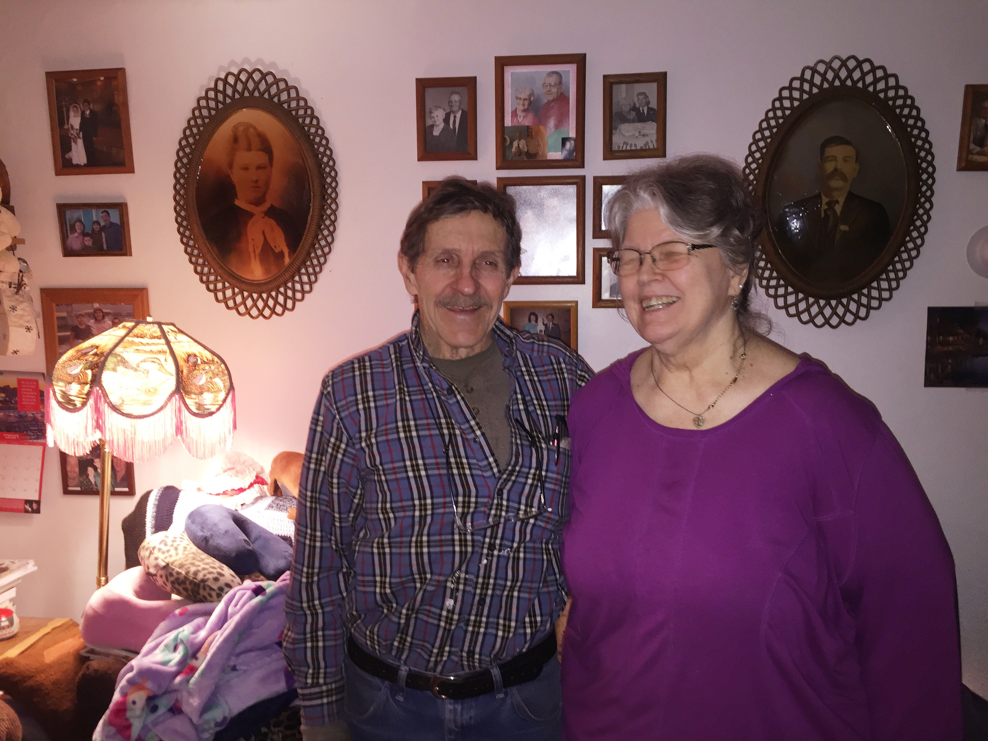 Shirley and Tom Clements tease each other as they pose in front of their wall of memories. (Photo by Anne Hillman/Alaska Public Media)
