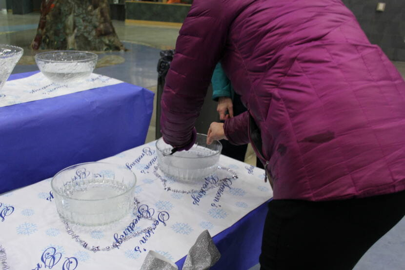 An attendee places a slip of paper with something they hope to let go of in the coming year into a bowl to let it dissolve at the Year of Kindness celebration on New Year's Eve. (Photo by Adelyn Baxter/KTOO)