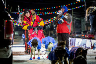 Mitch Seavey pulls his team past the finish line after officially checking off the Iditarod Trail. (Photo by David Dodman/KNOM)