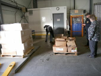 Petersburg community cold storage manager Marv King, wildlife trooper Cody Litster and Salvation Army major Loni Upshaw prepare two pallets of moose meat for distribution at the cold storage Thursday, December 7, 2017. (Photo by Joe Viechnicki/KFSK)