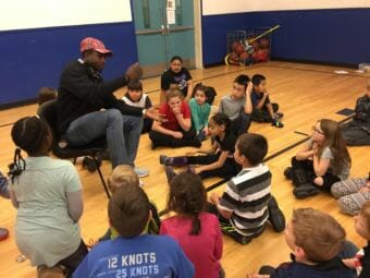 Kayrick Felton tells stories to children at the Woodland Park Boys & Girls Club in Anchorage while others prepare to present skits. (Photo by Anne Hillman/Alaska Public Media)