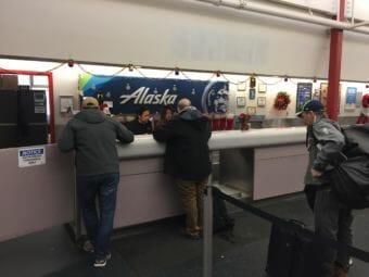 Unalaska Fire Chief Arlie Colvin, center, checks in for his flight Dec. 23, 2017. (Photo by Zoë Sobel/KUCB)