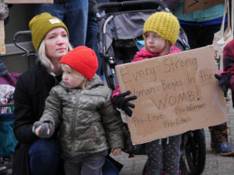 A woman and two children attend an anti-abortion rally outside the Alaska State Capitol on Monday, Jan. 22, 2018. The group Alaskans for Life organized the event.