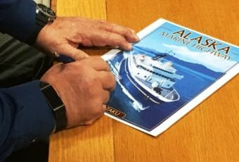 An official signs a poster of the ferry Taku at a ceremony for the sale of the ferry at Alaska Marine Highway headquarters in Ketchikan on Friday, Jan. 19, 2018.