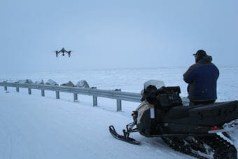 Dennis Davis flying his drone at the edge of Shishmaref a few days after a cold snap helped the sea ice freeze up late in January. (Photo by Zachariah Hughes/Alaska Public Media)