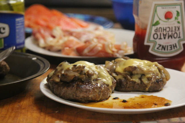 Dennis Davis's musk ox burgers, topped with Swiss cheese, sautéed onions and mushrooms, along with freshly sliced prosciutto and a home-made aioli. Or ketchup. (Photo by Zachariah Hughes/Alaska Public Media)
