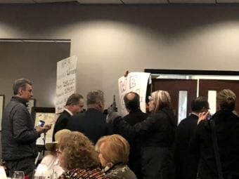 Protesters at an event featuring Sen. Lisa Murkowski and Rep. Don Young are quickly ushered out of the room on Monday, Feb. 19, 2018. (Photo by Elizabeth Harball/Alaska's Energy Desk)