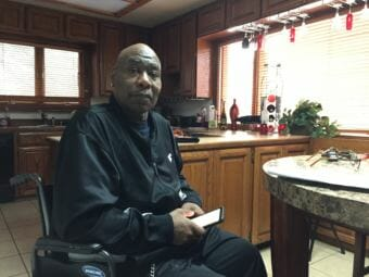 Dion Wynne sits in a wheelchair in his furnished rental. (Photo by Anne Hillman/Alaska Public Media)