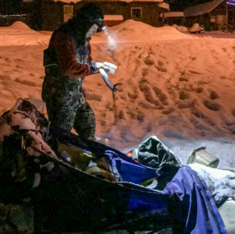 Whitehorse musher Marcelle Fressineau examines her ax at the Takotna checkpoint of the Iditarod on March 9, 2009. She says she had used the ax somewhere between Rohn and Nikolai to fend off bison.