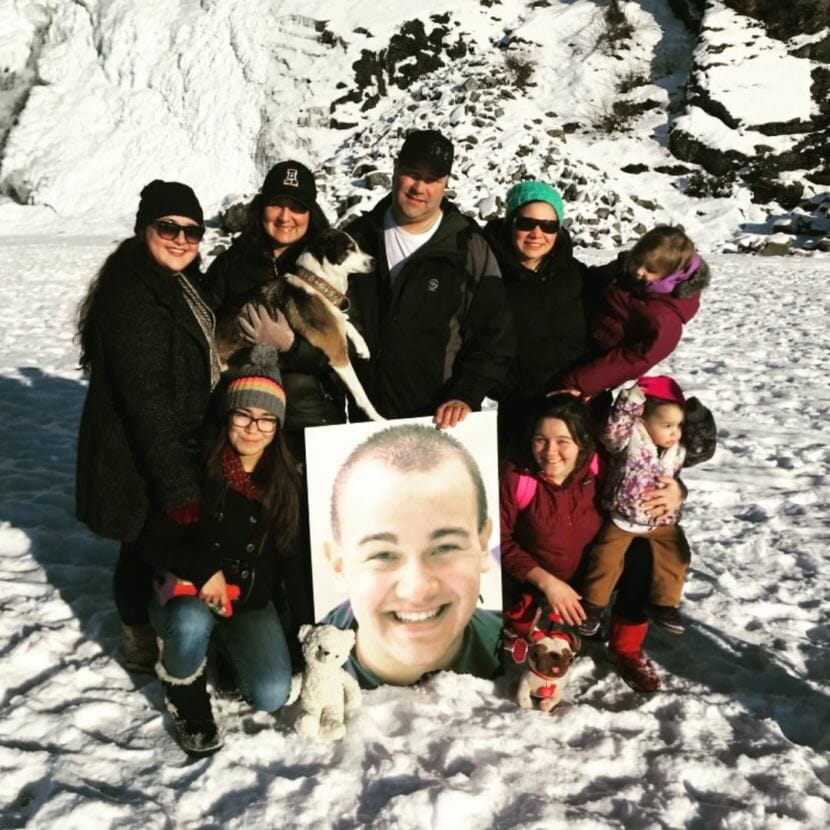 Family members pose with a portrait of Cody Eyre near the Mendenhall Glacier in Juneau in February 2018. Cody Eyre was killed by law enforcement in Fairbanks on Dec. 24, 2017, and his family is seeking more information about the incident.