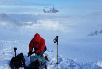 Roman Sorokin waits as USCG rescue swimmer Keith Williams descends from a Jayhawk helicopter in the distance (Photo courtesy Josh Joseph)