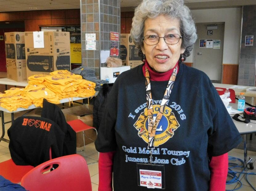 Mary Lekanof is a Juneau Lions Club member who volunteers before and during the Gold Medal games. Here's she works at the merchandise table. (Photo by Ed Schoenfeld/CoastAlaska News)