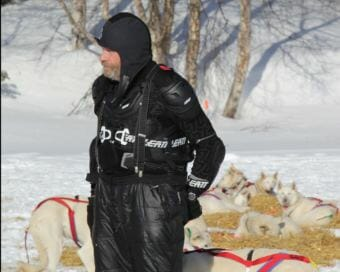 Jim Lanier handling his dogs at the Finger Lake checkpoint in his protective mountain biking gear. (Photo by Zachariah Hughes/Alaska Public Media)