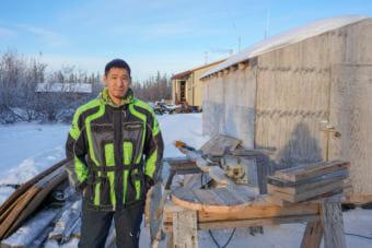 Ben Sherman Jr. stands outside his home in Noatak where he builds sleds. (Hillman/Alaska Public Media)
