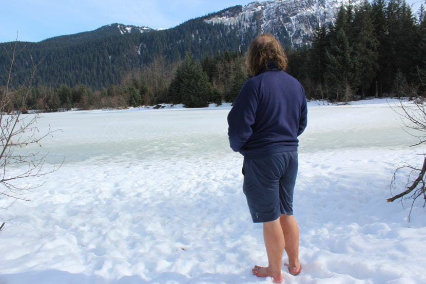 """Barefoot Guy"" Ezra Strong looks out on Dredge Lake during a hike. (Photo by Adelyn Baxter/KTOO)"