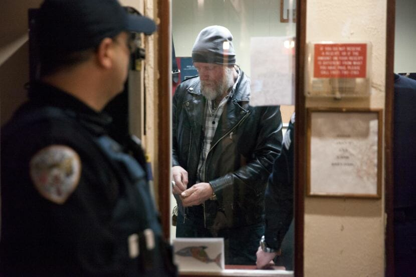 Juneau police officers confer as they arrest Chuck Cotten, property manager at the Bergmann Hotel. Cotten was responsible for removing residents from their rooms before Friday March 10, 2017 in Juneau, Alaska. The building was later condemned. (Photo by Rashah McChesney/Alaska's Energy Desk)