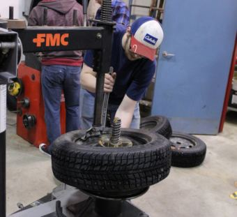 Senior Dylan Rice adjusts a tire during an automotive class in the UAS Technical Education Center. (Photo by Adelyn Baxter/KTOO)