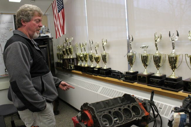 Juneau-Douglas High School automotive instructor Steve Squires points out some of the awards students have won over the years for technical knowledge. (Photo by Adelyn Baxter/KTOO)