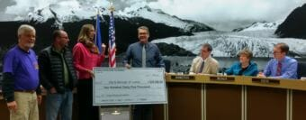 Juneau Community Foundation Executive Director Amy Skilbred presents Juneau City Manager Rorie Watt a novelty check for $235,000 in donations for Project Playground on April 2, 2018.