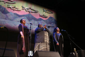 "Three women sing in front of a backdrop of metallic fish, the northern lights and a mountain scene. Erika Lee, Jocelyn Miles and Salissa Thole sing as the group ""Brown Sugar"" at the 44th Annual Alaska Folk Festival in front of the backdrop created by the JDHS Art Club. (Photo by Annie Bartholomew/KTOO)"