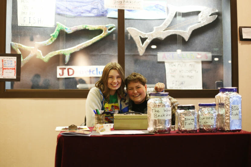Two people sit at a table at the Alaska Folk Festival in front of fish sculptures. Juneau-Douglas High School Art Club co-President Riley Stadt and Secretary Theo Houck auction off fish sculptures to raise money for the club's trip to Region V Art Fest. (Photo by Annie Bartholomew/KTOO)