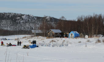 The austere Iditarod checkpoint, with just two major shelter structures, and tents or converted out buildings set up for Iditarod. (Photo by Zachariah Hughes/Alaska Public Media)