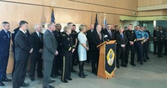 Alaska Gov. Bill Walker, flanked by more than 30 law enforcement officials, holds a press conference on Friday, May 18, 2018, at the state crime lab in Anchorage.