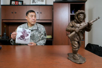 Then-Lt. Col. Wayne Don of the Alaska Army National Guard holds a photo of his uncle, Sam Herman, who served with the Alaska Territorial Guard during World War II in his office on Feb. 27, 2015. Herman is pictured during his subsequent service with the Alaska Army National Guard. A statuette of an ATG scout keeps vigil on Wayne's desk.