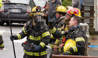 A group of firefighters talk at the corner of Fifth and Franklin streets after the house fire there on May 28, 2018. (Photo by David Purdy/KTOO)