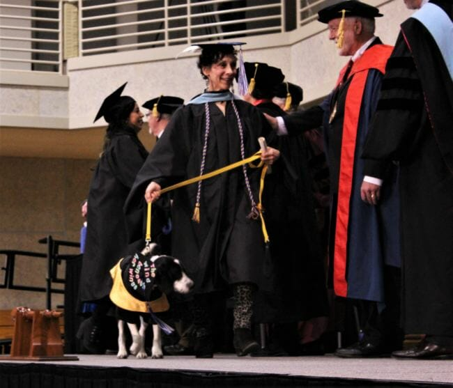 UAS graduate Barbara Van Flein walks across the stage with her service dog, Capone. (Photo by Adelyn Baxter/KTOO)