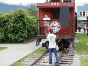 Tourists in Skagway take pictures with a White Pass and Yukon Route Railroad train car in 2017. (Photo by Emily Files/KHNS)
