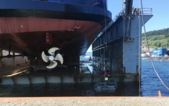 Vigor Alaska shipyard workers board the drydock from a skiff before the ferry Tazlina is lowered into the water for the first time on May 16, 2018 in Ketchikan.