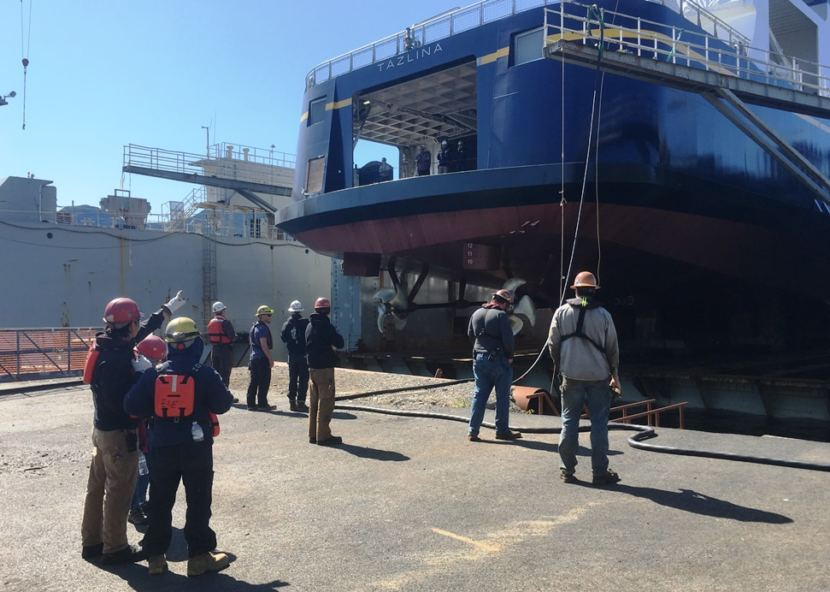 Vigor Alaska shipyard workers gather to watch the Tazlina get lowered into the water at the shipyard's drydock in Ketchikan on May 16, 2018.