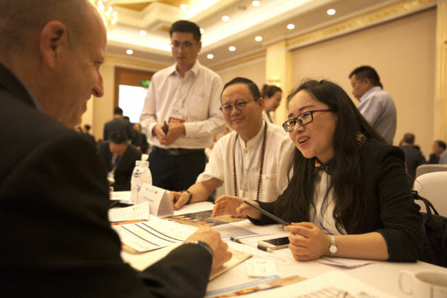 "Ron Risher of Icicle Seafoods talk to Crescent Xuan, Manager of International Trade for the Sichuan Jinggong Flavor Co., during a ""speed dating"" event designed to bring companies with Alaska products to Chinese consumers on Tuesday, May 22, 2018, in Chengdu, China. (Photo by Rashah McChesney/Alaska's Energy Desk)"