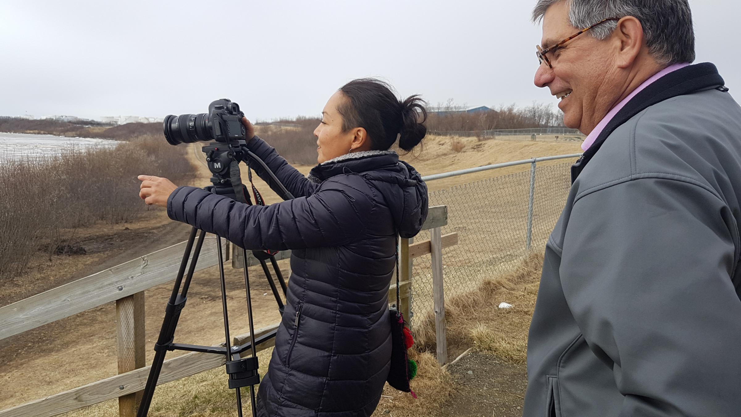 Videographer Jacqueline Cleveland, left, films the Kuskokwim River on May 3, 2018, with Mark Trahant as they report on the Dental Health Aide Therapist Program in Bethel. (Photo by Christine Trudeau/KYUK)