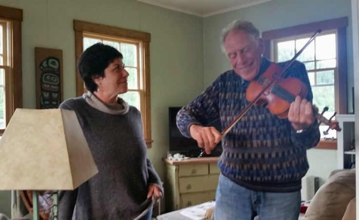 Avrum Gross plays the fiddle as his oldest daughter, Jody Gross, listens. Avrum was a Juilliard trained violinist as a youth, quit as an adult, but came back to it as a fiddler after moving to Alaska. (Photo courtesy Jody Gross)